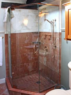 Luxurious marble shower with copper fixtures and overhead and hand showers