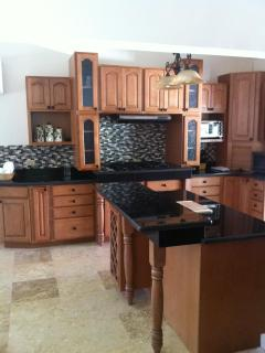 Fully equipped gourmet kitchen in maple with black grantite counters, travertine marble floors.