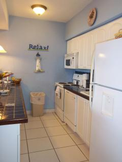 The galley  kitchen is well equiped with cooking utensils, pots and pans, dishes etc.