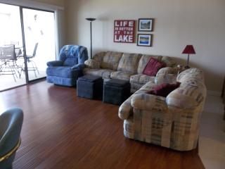 Living room area with sleeper sofa, love seat, recliner, flat screen TV, wood floors