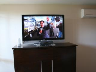 Large HDTV on top of MurphyBed with Split AC in top right corner