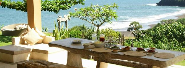 A second dining table is positioned on an outdoor terrace with beautiful view extending up the coast