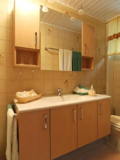 Bathroom with shower, hairdryer, slippers, bathrobes, towels and amenities