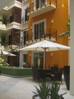 Entry level atrium courtyard with fountain, table and chairs with parasol