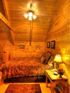 Upstairs bedroom with vaulted ceiling and wooden beam