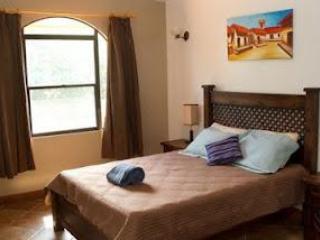 Dormitorio principal en suite con cama queen, TV de pantalla plana y baño privado