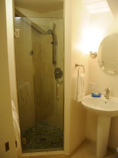 Pedestal sink and a river-rock bottom shower in loft bathroom.
