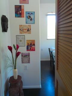 Buddha mask, straw Ganesh table and Music Circle Hawaii posters grace the wall outside the louvered door.