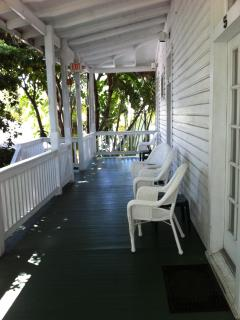 SHARED PORCH W/ SITTING CHAIRS ON  LARGE, WRAPAROUND BALCONY.