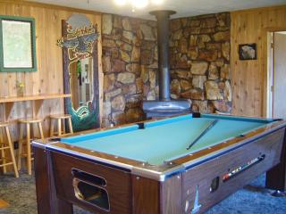 Pool table, wood stove bar counter top with setting.