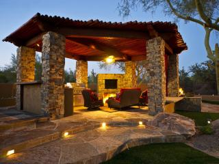 outdoor covered ramada featuring BBQ, fireplace, TV & seating area. attached gas fire pit