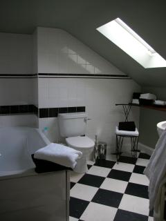 Stylish black and white bathroom with large double ended bath tub