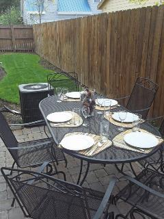 Side yard with patio, dining table and gas grill