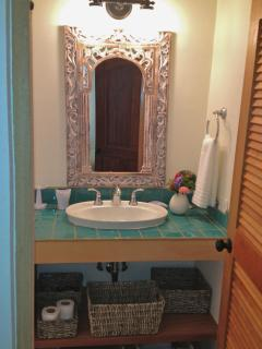 The master bath is bright and fully tiled with baskets for your toiletries.
