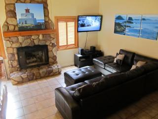 Living room with 46 inch HDTV, stone fireplace and sofa
