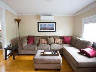 Living room with comfy suede couch and signed print of downtown skyline
