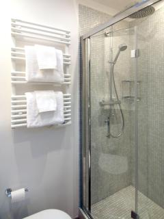 The shower is lined with glass mosaic tiles and a towel warmer keeps your towels warm and dry