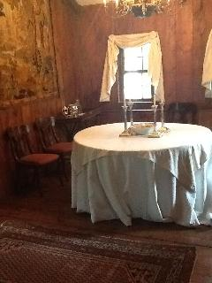 Wood paneled peaked roof dining room with tapestry in background