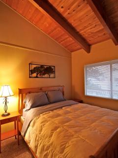 Guest room with queen bed and vaulted ceilings