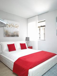 King size bed with memory foam mattress, red coloured pillows and soft bed linen