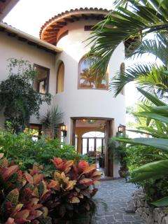 Pass through the gate and you are surrounded by a tropical garden that extends far down the property.