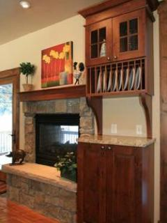 Kitchen two-sided fireplace shared with deck overlooking Jane Creek and the national forest