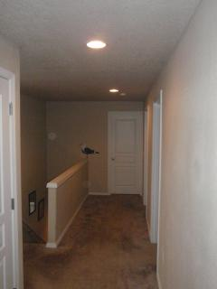 Upstairs hallway, facing bathroom with rooms on right, laundry on left