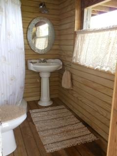 Master Bath includes shower, eco-low-water usage toilet, wicker chest, pedestal sink and open view