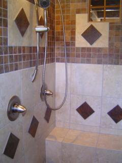 The spa inspired, main level shower has 3 shower heads, a bench, 2 sconces and 2 windows.