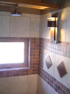 Another view of the luxurious spa-like main shower showing one shower head, one sconce and 1 window.