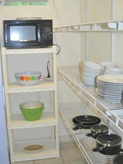 Fully stocked pantry with dishes, pots and pans and microwave