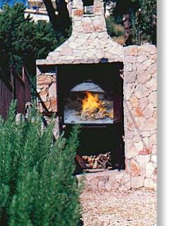 large barbecue stocked with firewood and coal - prepare your own grilled fish, with fresh rosemary
