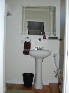 All bathrooms are identical to this one: pedestal sink, standing shower, and commode