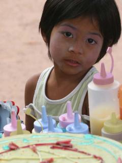 Little girl in the village waiting for her pancake