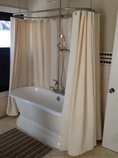 Vintage tub shower combination in a spacious bathroom.