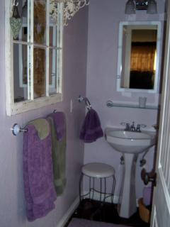 Pedestal sink and purple stone floors.