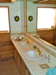 Second bathroom features two sinks, as well as another tub and shower.