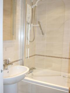 Modern, fully tiled bathroom with electric shower over the bath