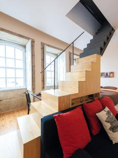 Stairs are next to the sofa.