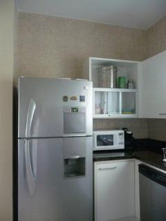 Corner of kitchen showing 2-door fridge/freezer, modern cabinets