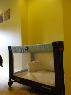 The yellow room with optional play pen or infant crib, with a crib mattress available upon request