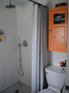 The newly remodeled bathroom features an antique medicine cabinet,