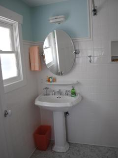 a pedestal sink and vintage light fixture,