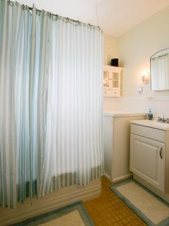 Bathroom with tub/shower combo, window, sink & vanity, toilet, tile floors