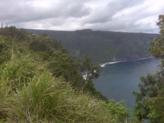 Cliff's edge with Waipio Valley's black sand beach below