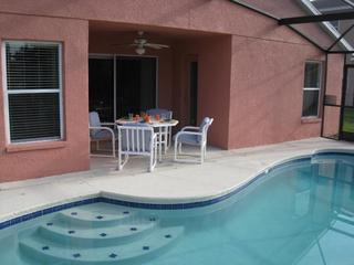 Pool deck area, patio furniture for enjoying outdoor meals and sun loungers.