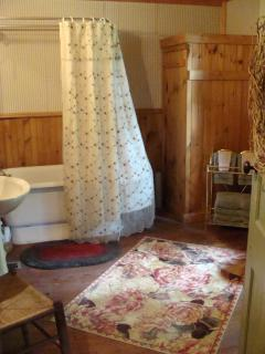 large bathroom with antique pedestal tub & dresser