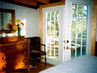 Main Bdrm with Q bed, antique dresser & double french doors to add lots of light. private deck