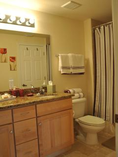 Comfortable bathroom with his and her sinks, tub/shower.