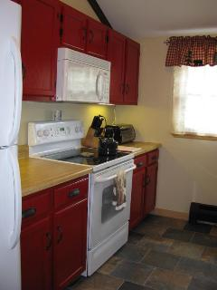 Kitchen with full sized refrigerator, stove and microwave